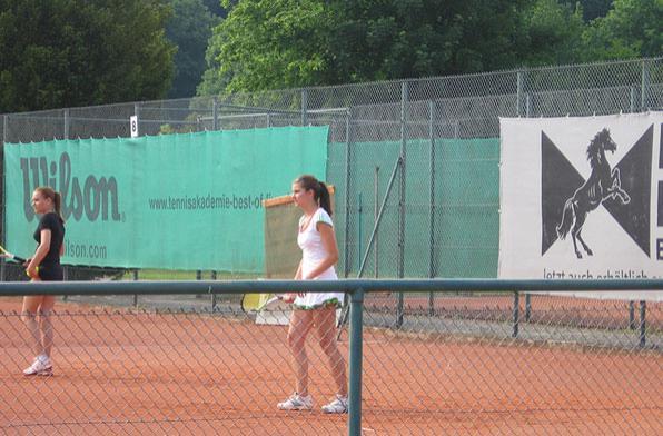 Ученицы теннисной академии тренируют подачу на открытом корте